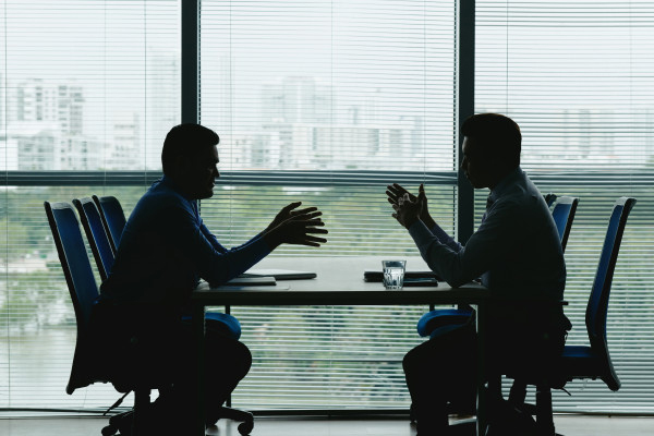 Two people having a discussion in a conference room